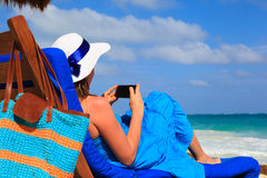 Woman with cell phone on tropical beach Royalty Free Stock Photos
