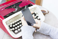 Woman with cell phone and typewriter Royalty Free Stock Photography