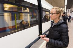 Woman with a cell phone waiting for metro. Young casual woman with a cell phone in her hand waiting on the platform of a metro station for metro to arrive Stock Images