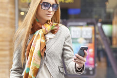 Woman with cell phone walking Royalty Free Stock Images