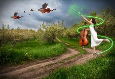 Woman with cello and dragon violins. Woman in white dress making magic with her commissure wand and dragon violins with bat wings flying away in the sky royalty free stock photography