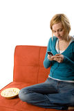 Woman with cellphone. A young woman is sitting on a orange-brown couch holding a cellphone and typing a text message. There is a bowl of popcorn next to her. She Stock Image