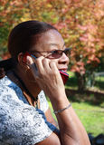 Woman on cellphone. A portrait of a middle aged African American woman outdoors talking on a cellphone on a bright, autumn day stock images
