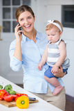Woman with cellphone carrying daughter by kitchen counter Stock Photos