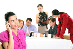 Woman with cellphone,colleagues in the background. Business team - women with cellphone on the foreground Stock Photography