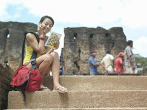 Woman With Cellphone And Guidebook Against Old Ruins Stock Photo