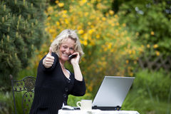 Woman with cellphone and laptop posing thumbs up Stock Photography