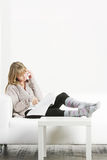 Woman with cellphone and magazine laying on sofa Royalty Free Stock Photography