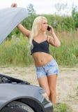 Woman with cellphone near broken car. Stock Photo