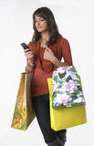 Woman with cellular phone. Pretty young woman with shopping bags and cellular phone Royalty Free Stock Photography