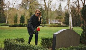Woman at the cemetery paying respects with fresh flowers Royalty Free Stock Images