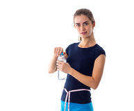 Woman with centimeter opening a bottle of water Royalty Free Stock Image