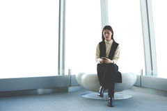 Woman CEO with cell telephone in hands  is sitting in modern office interior against skyscraper window Stock Photos