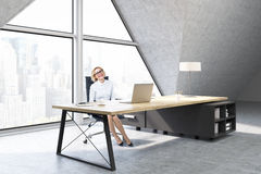 Woman in a CEO office with triangular window. Woman sitting in a CEO office with a large triangular window, a large table with a notebook and a lamp. 3d royalty free stock photo