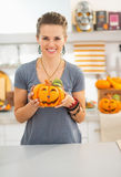 Woman with ceramic pumpkin in halloween decorated kitchen Royalty Free Stock Photo