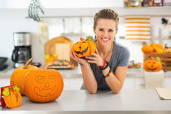Woman with ceramic pumpkin in halloween decorated kitchen Stock Photography