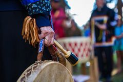 Woman in ceremonial clothing is holding her sacred drum stock photography