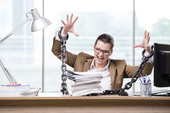 The woman chained to her working desk Stock Photos