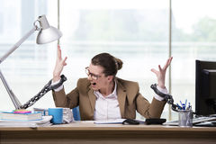 The woman chained to her working desk Royalty Free Stock Images