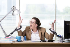 The woman chained to her working desk Stock Images