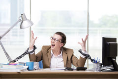 The woman chained to her working desk Stock Photo
