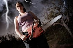 Woman with chainsaw. Vampire with chainsaw on sky background stock photography