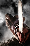 Woman with chainsaw. Vampire with chainsaw on sky background royalty free stock photos