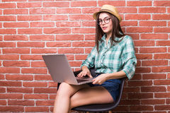 Woman on chair in casual wear is using a laptop Stock Photography
