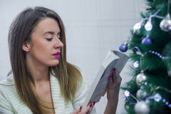 Woman in chair in front of Christmas tree reading book. Woman reading book near Christmas tree. Royalty Free Stock Photos