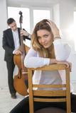 Woman on chair and man with contrabass Royalty Free Stock Images