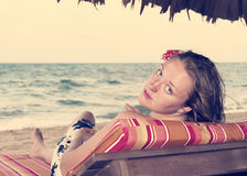 Woman on a chair by the ocean with a flower in her hair, retro Royalty Free Stock Photo