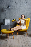 The woman in a chair with phone Royalty Free Stock Photography