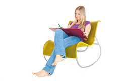 Woman on chair taking notes Stock Photography