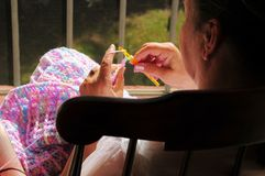 Woman in chair using crochet. Woman sitting in a wooden rocking chair, on a patio, knitting a blanket, using a crochet and yarn Stock Photo