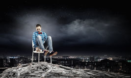 Woman in chair. Young woman sitting in chair on ruins Stock Photo