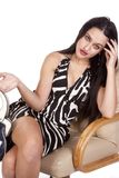 Woman in chair in zebra dress Stock Photo
