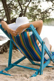 Woman in chaise longue. Woman in white hat sitting in chaise longue stock photography