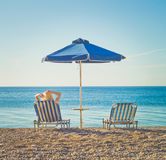 Woman in a chaise-longue under an umbrella. Woman on southern beach resting in a chaise-longue under an umbrella. Summer travel. Beach vibes Stock Image
