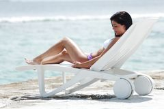 Woman in chaise-lounge near sea. Woman lying in chaise-lounge on sea background royalty free stock image