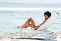 Woman in chaise-lounge near sea. Woman lying in chaise-lounge on sea background royalty free stock images