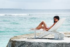 Woman in chaise-lounge near sea Royalty Free Stock Images