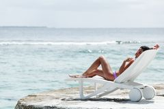 Woman in chaise-lounge near sea Royalty Free Stock Photo
