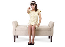 Woman on Chaise Lounge Pointing. Stylish retro female sitting on a chaise lounge or sofa on white background royalty free stock photography