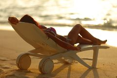 Woman in chaise-lounge relaxing on beach. Woman in chaise-lounge relaxing on sunset beach royalty free stock photo