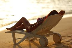 Woman in chaise-lounge relaxing on beach Royalty Free Stock Photography