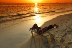 Woman in chaise-lounge relaxing on beach Royalty Free Stock Photos
