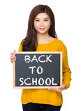 Woman with chalkboard showing phrase of back to school Royalty Free Stock Image