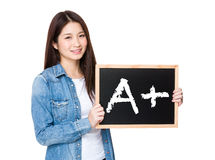 Woman with chalkboard showing A plus mark Stock Images