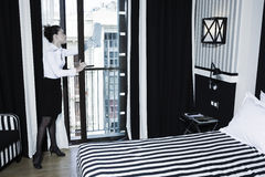 Woman chambermaid cleaning in a hotel bedroom Stock Photography