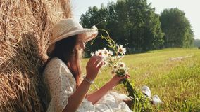 Woman with chamomiles in the meadow. Beautiful girl in white dress and straw hat sitting near haystack in meadow with bouquet of daisies in arms and smiles stock video